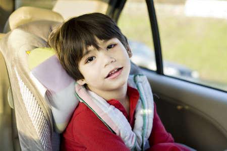 handicap people: Ni�o de cuatro a�os con par�lisis cerebral, sentado en el carseat Foto de archivo