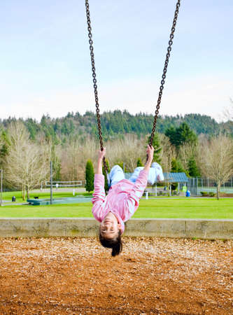 Happy little nine year old part Asian girl swinging upside down Stock Photo - 8832453