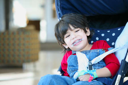 cerebral palsy: Cute disabled boy with cerebral palsy smiling in stroller Stock Photo