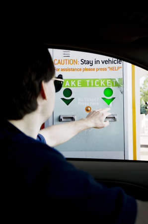 tollway: Man taking toll ticket from machine Stock Photo
