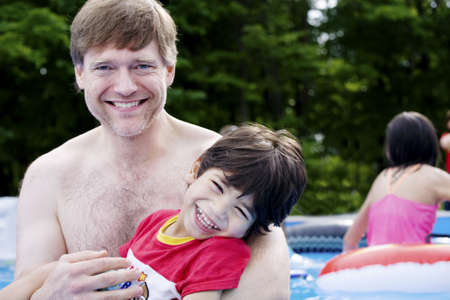 Father holding disabled son in pool Stock Photo - 9018596