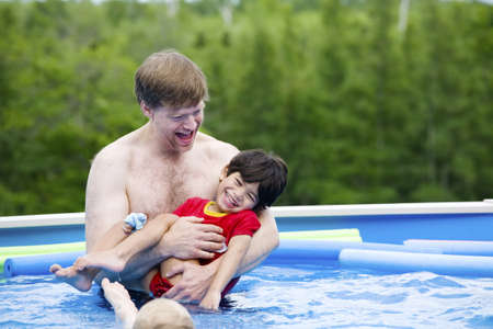 Father holding disabled son in pool Stock Photo - 9018595