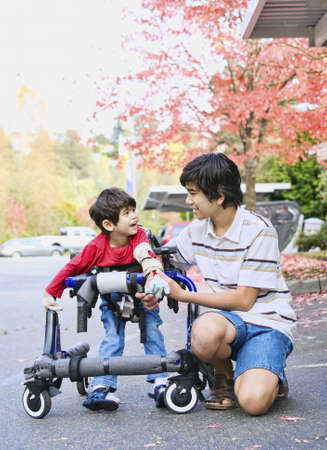disabled person: Teen boy with disabled little brother in walker out walking  Stock Photo