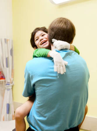 cerebral palsy: Little boy with cerebral palsy in doctors office, laughing with his father