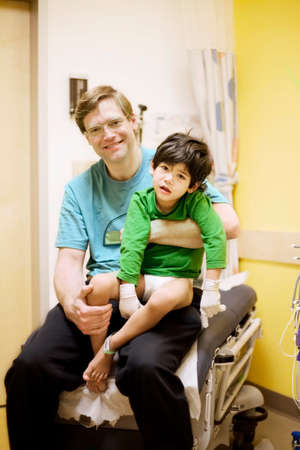 Father holding his sick disabled son in doctors office photo