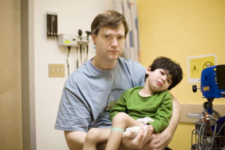somber: Worried father holding his sick disabled son in doctors office