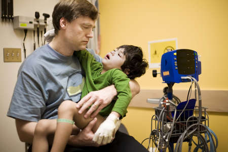 disable: Worried father holding his sick disabled son in doctors office