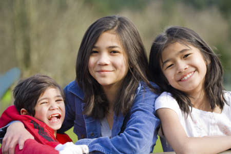Two sisters and their disabled little brother sitting together at the park, biracial part Thai- Scandinavian descent. photo