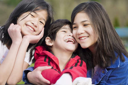 Two sisters and their disabled little brother sitting together at the park, biracial part Thai- Scandinavian descent.