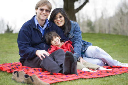 Father and mother sitting at park with disabled son, interracial family photo