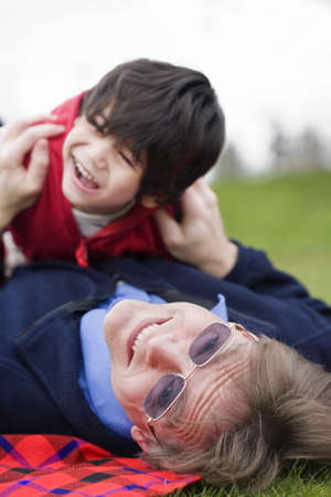 Father playing with disabled son on grass at park photo