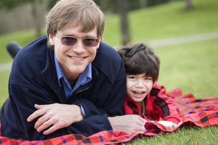 Father lying on blanket with disabled son at park Stock Photo - 9310868