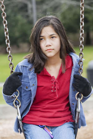 beautiful preteen girl: Angry, sad preteen girl sitting on swing Stock Photo