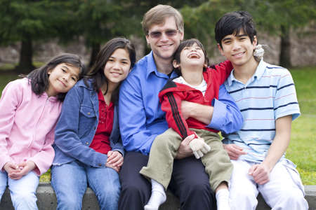 Happy interracial family enjoying day at park with disabled son photo