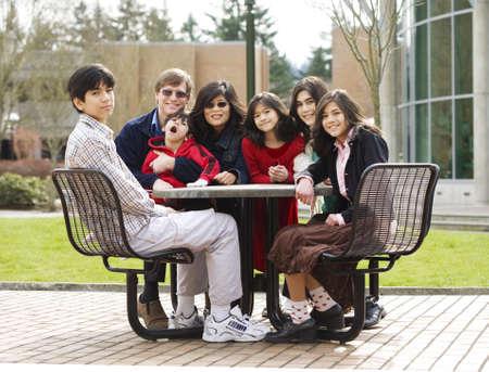 ni�os discapacitados: Hermosa familia interracial sentados juntos al aire libre, con el hijo de padre celebraci�n deshabilitado Foto de archivo