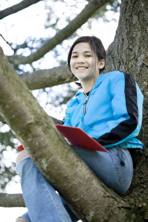 Preteen girl sitting in tree writing in journal or notebook photo
