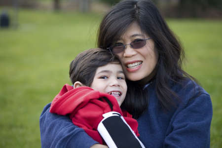 Beautiful asian mother holding her disabled son at park photo