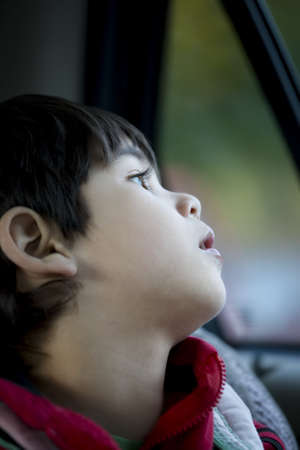 Handsome four year old boy looking quietly out car window Stock Photo