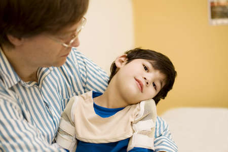 Father holding disabled son in doctors office