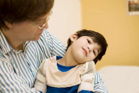enfants handicap�s: P�re tenant fils handicap� dans un cabinet de m�decin