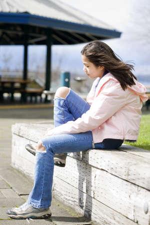 Preteen girl tying shoes outdoors near lake photo