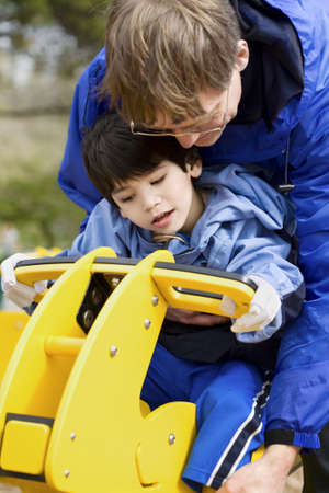 Father helping disabled son play on playground equipment Stock Photo