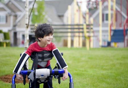 discapacitados: Ni�o de cuatro a�os permanente en walker cerca de un parque infantil de desactivado