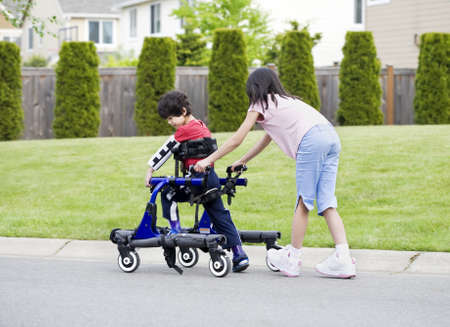 babysit: Big sister helping younger disabled brother to walk in his walker outside Stock Photo