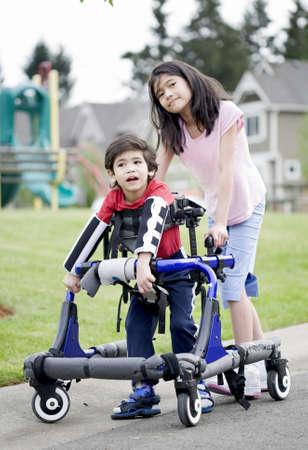 enfants handicap�s: Grande s?ur aidant les plus jeunes fr�re handicap� � marcher dans sa marchette en dehors