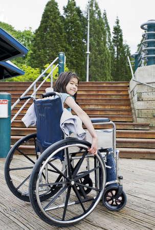persona en silla de ruedas: Joven niña de nueve años en silla de ruedas en frente de las escaleras Foto de archivo