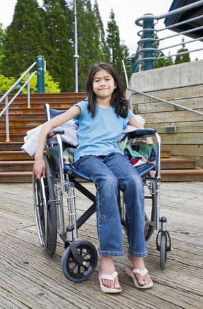 Young nine year old girl in wheelchair in front of stairs photo