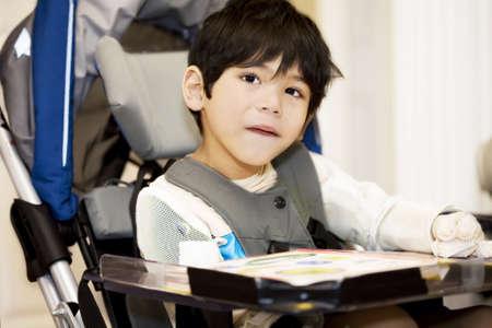 personas discapacitadas: Desactivado el niño de cuatro años estudiando o leer en silla de ruedas