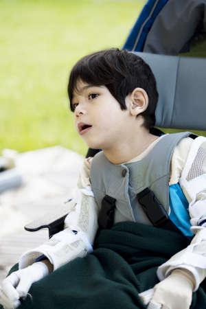 Vier jaar oude jongen uitgeschakeld met cerebrale parese buiten zitten in rolstoel Stockfoto