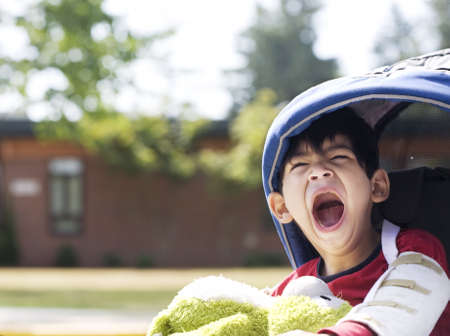 Disabled five year old boy in wheelchair in front of school, yawning