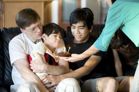 Disabled five year old boy blowing out birthday candles with family photo