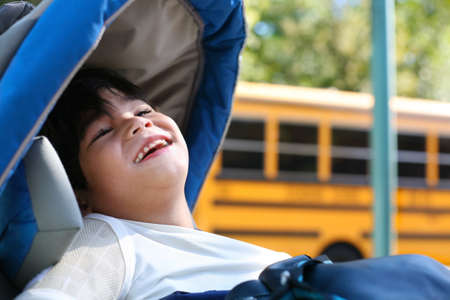 school year: Disabled five year old boy in wheelchair outdoors by school bus
