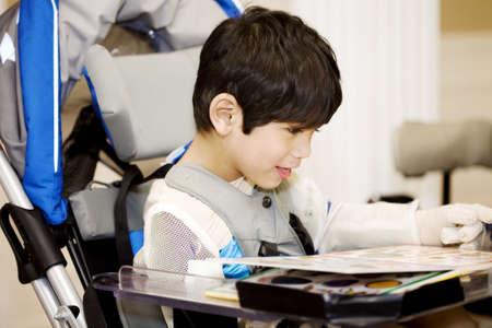 personas discapacitadas: Discapacitados cuatro a�os de edad, ni�o de estudiar o leer en la silla de ruedas Foto de archivo