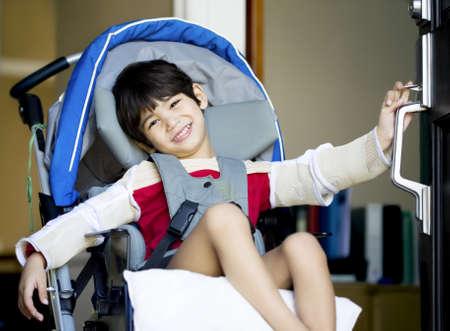 discapacidad: Guapo chico de cuatro años con discapacidad en silla de ruedas abrir puerta, sonriendo con una bienvenida