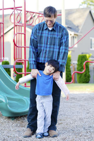 Father helping disabled four year old son to play at playground photo