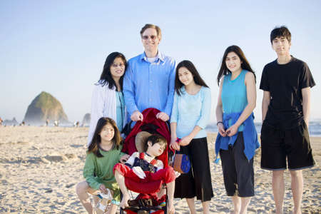 cerebral palsy: Large family of seven standing on the beach by the ocean. Boy in stroller is disabled with cerebral palsy.