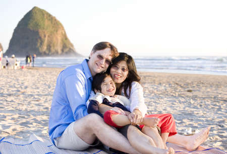 Small family with disabled little boy sitting at the beach by the ocean photo