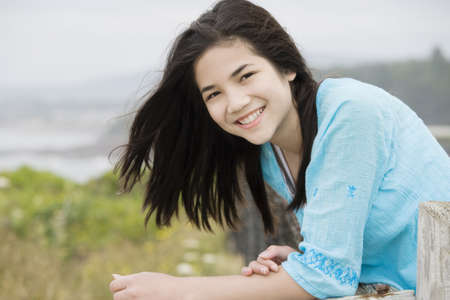 asian preteen: Preteen biracial girl with a beautiful smile, overlooking the ocean shore Stock Photo
