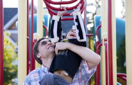 Actieve uitgeschakeld vijf jaar oude jongen die op het klimrek met zijn vader Stockfoto