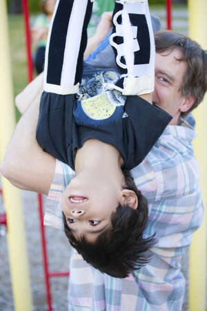 Active disabled five year old boy playing on the  monkey bars with his father photo