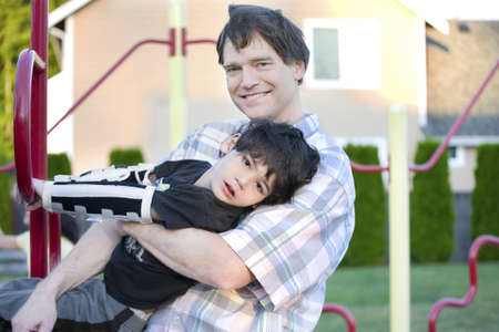 Father helping disabled son to play at playground photo