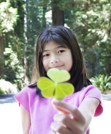 Ten year old Asian girl holding out large three leaf clover photo