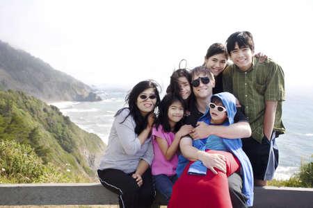 Multiraciale gezin van zeven zitten door de Stille Oceaan. Jongetje is uitgeschakeld met een hersenverlamming.