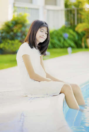Ten year old girl repaxing by swimming pool, smiling photo