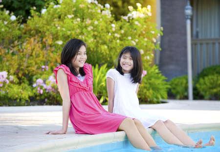 swim race: Two young girls, biracial, part- Asian, enjoying time sitting by pool.