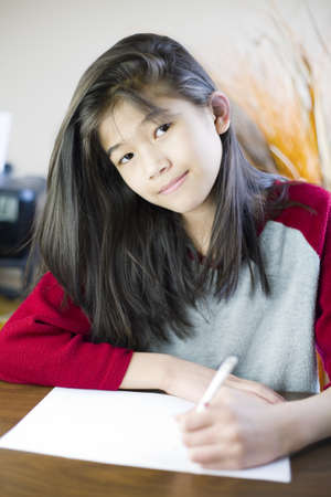 person writing: Ten year old biracial girl writing or drawing on paper